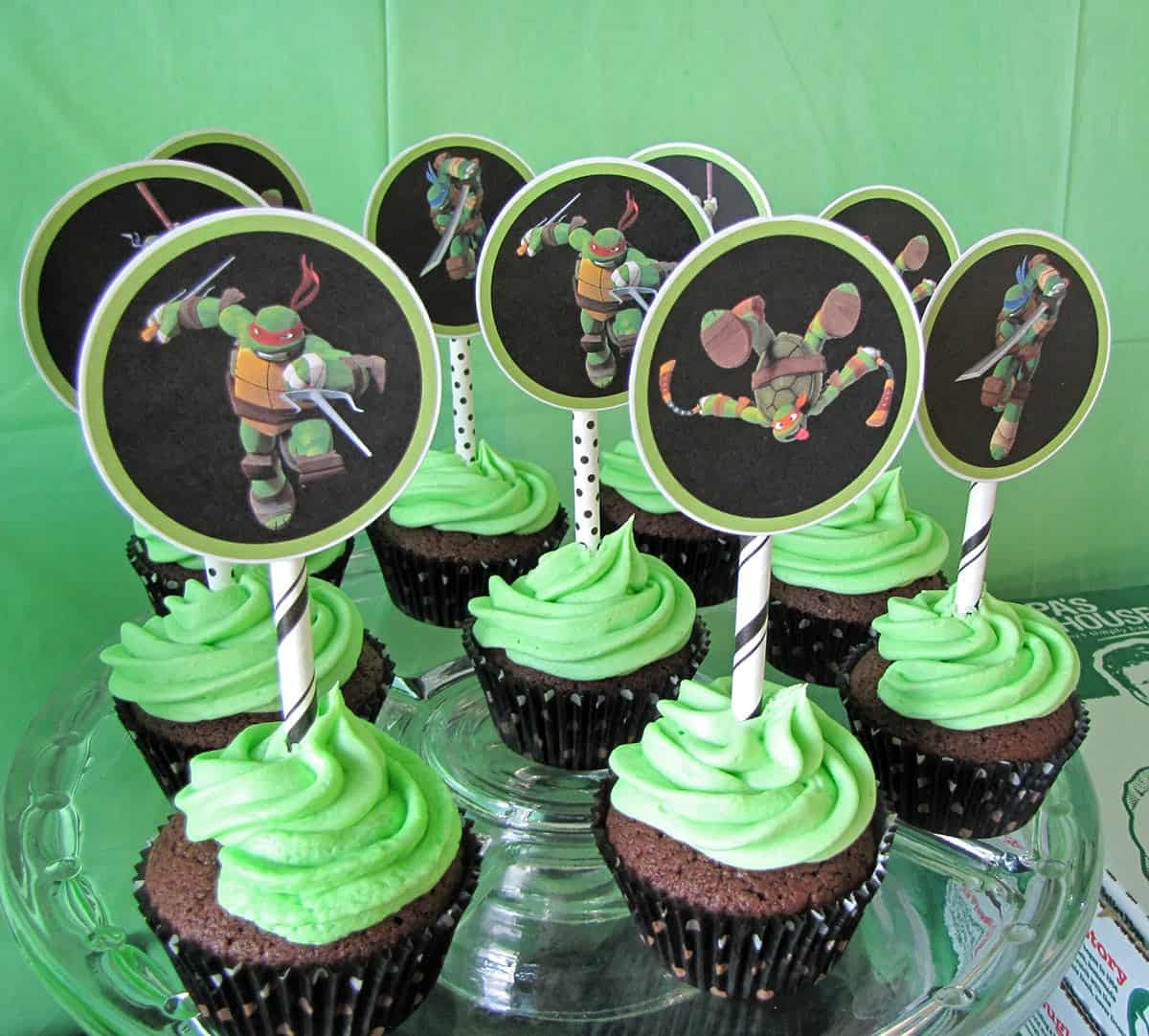 Ninja Turtle Cupcakes-chocolate cupcakes with bright green icing and ninja turtle cupcake toppers on glass serving tray.