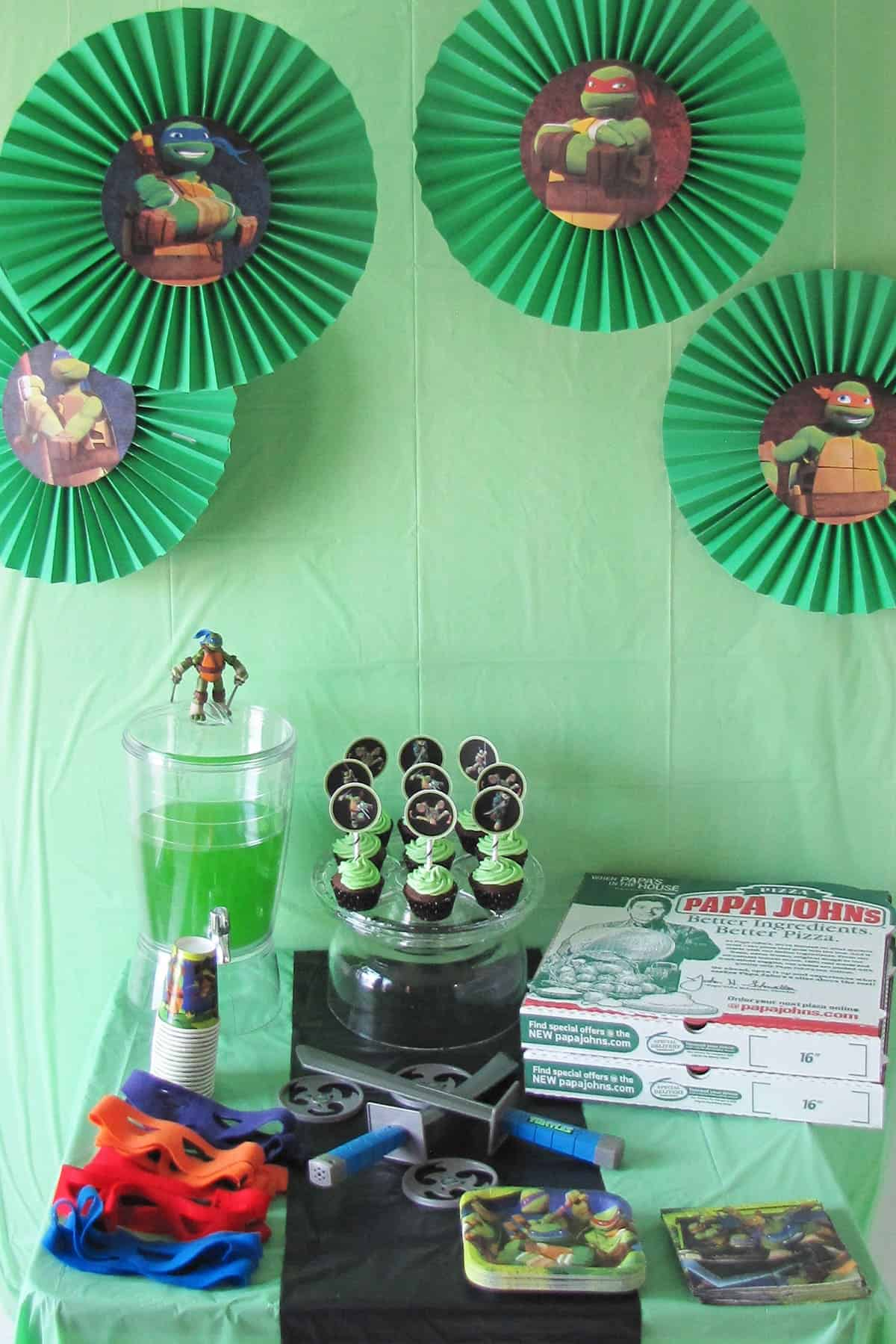Ninja Turtle themed party table with cupcakes, green punch, pizza, masks, swords, ninja turtle paper products, and green backdrop with paper fans.