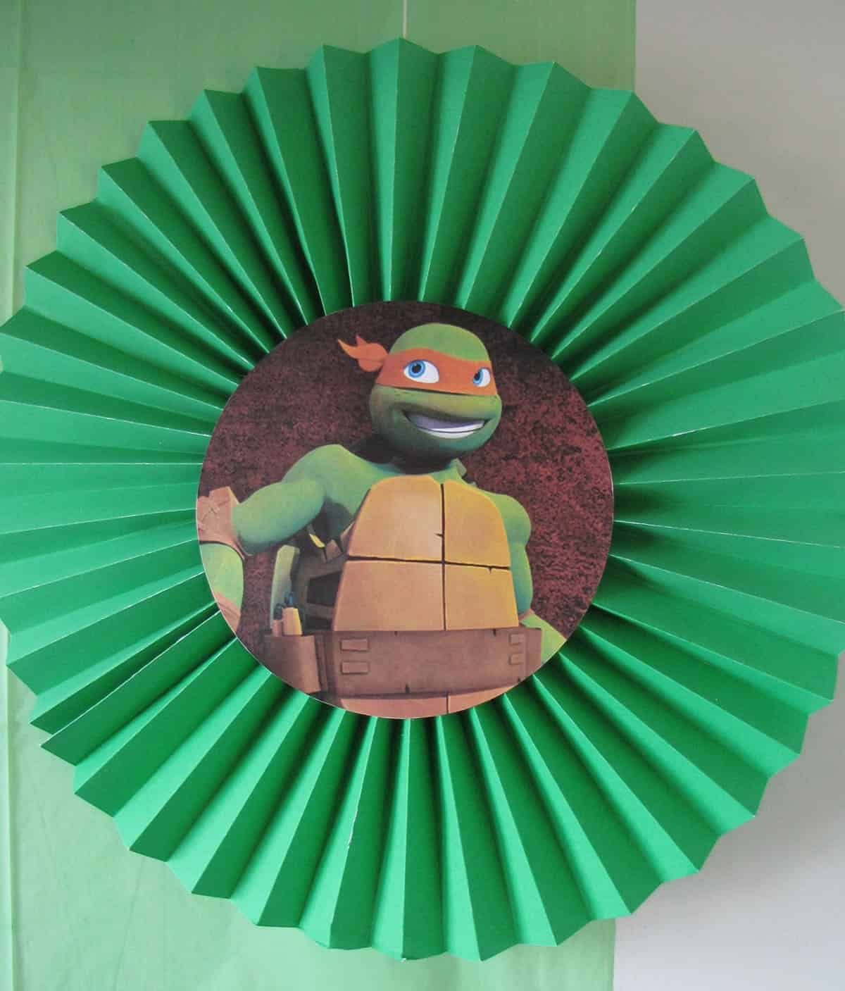 Ninja Turtles green party fan with Michelangelo in front of green backdrop