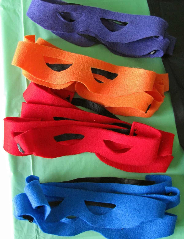 Teenage Mutant Ninja Turtle felt DIY masks stacked on green table cover.
