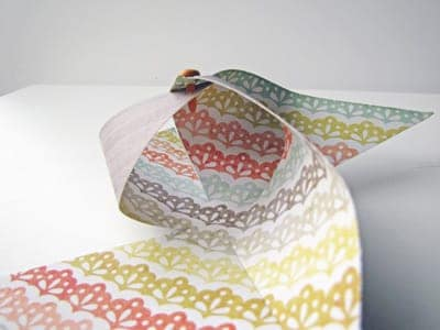 Colorful craft paper partially folded into DIY pinwheel shape on white surface.