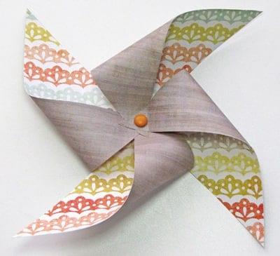 Front of dual gray and rainbow colored DIY pinwheel on white surface.