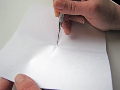 Utility knife in hand cutting through center of white template for making pinwheels.