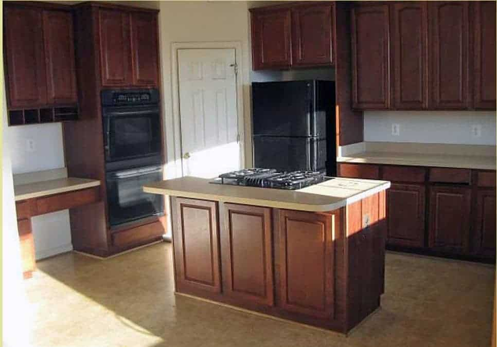 Traditional kitchen with island before makeover with dark wood cabinets, beige countertops, and black appliances.