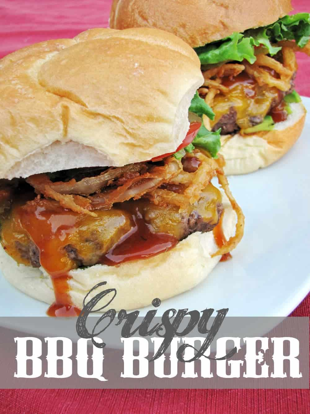 Two cheeseburgers topped with crispy fried onion straws. lettuce, tomato, and BBQ sauce on white plate.