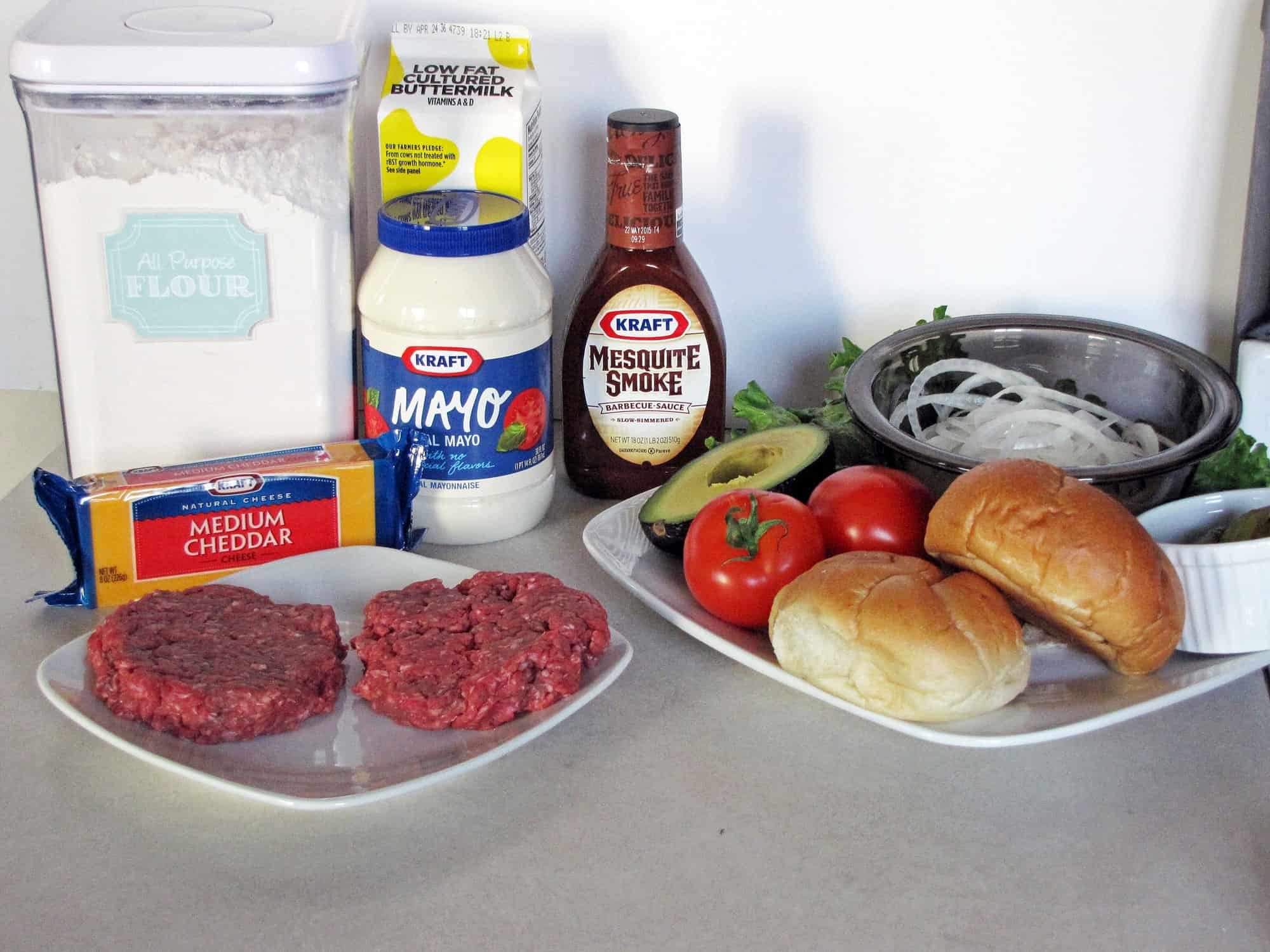 Ingredients for crispy onion string BBQ cheeseburgers on white plates-Beef, onion, tomato, avocado, buns, pickles, BBQ sauce, cheddar, mayo, buttermilk, and all purpose flour.