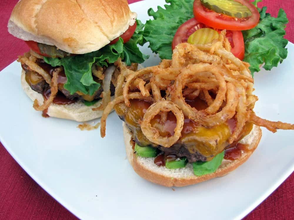 Crispy fried onion strings on BBQ open faced BBQ cheeseburger next to assembled burger on white plate with veggie toppings.