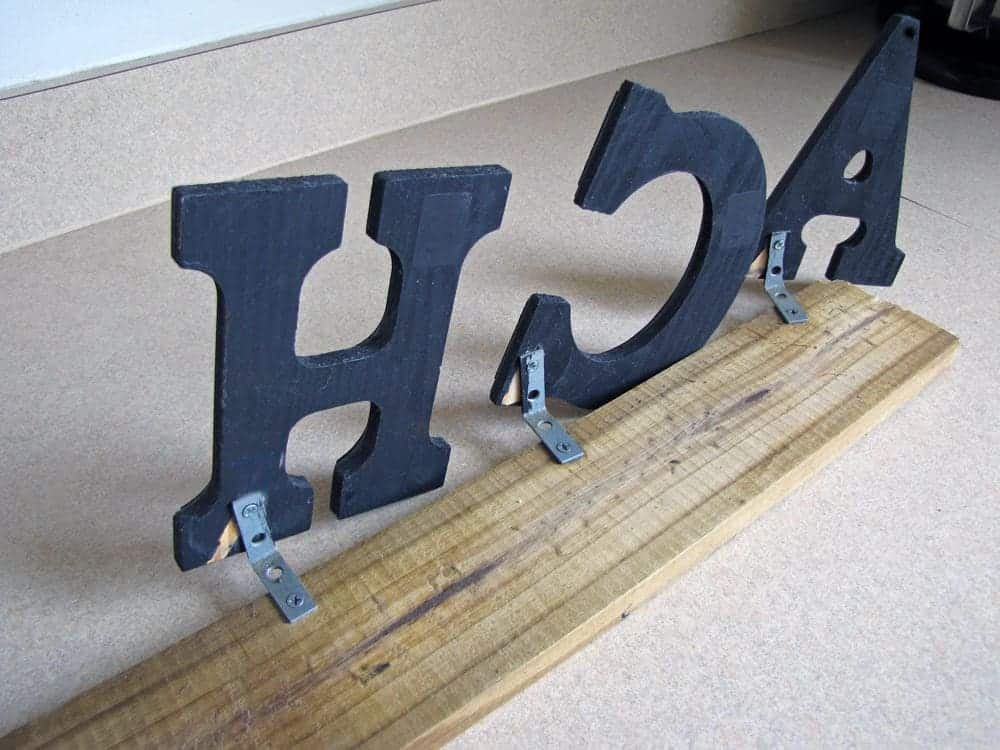 Wooden plank with black block letters attached with metal L brackets on beige countertop.