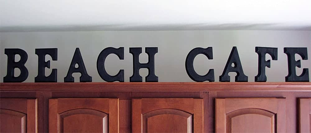 An easy DIY idea to decorate above kitchen cabinets with wood letters Beach Cafe