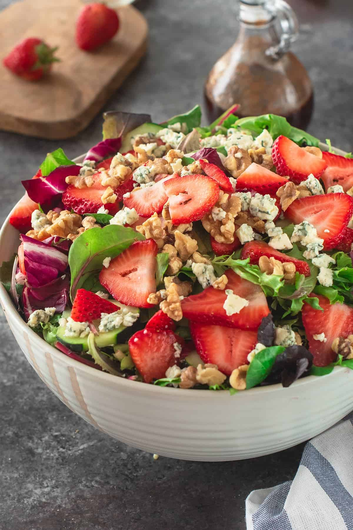 Strawberry Salad topped with whole strawberries, blue cheese, and walnuts with Glass dressing bottle of balsamic vinaigrette.