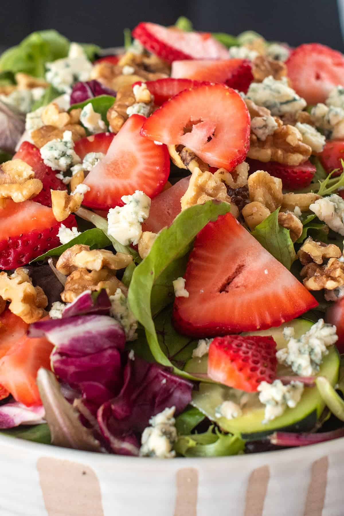 Closeup of Strawberry Spinach Salad in white bowl with beige accent.
