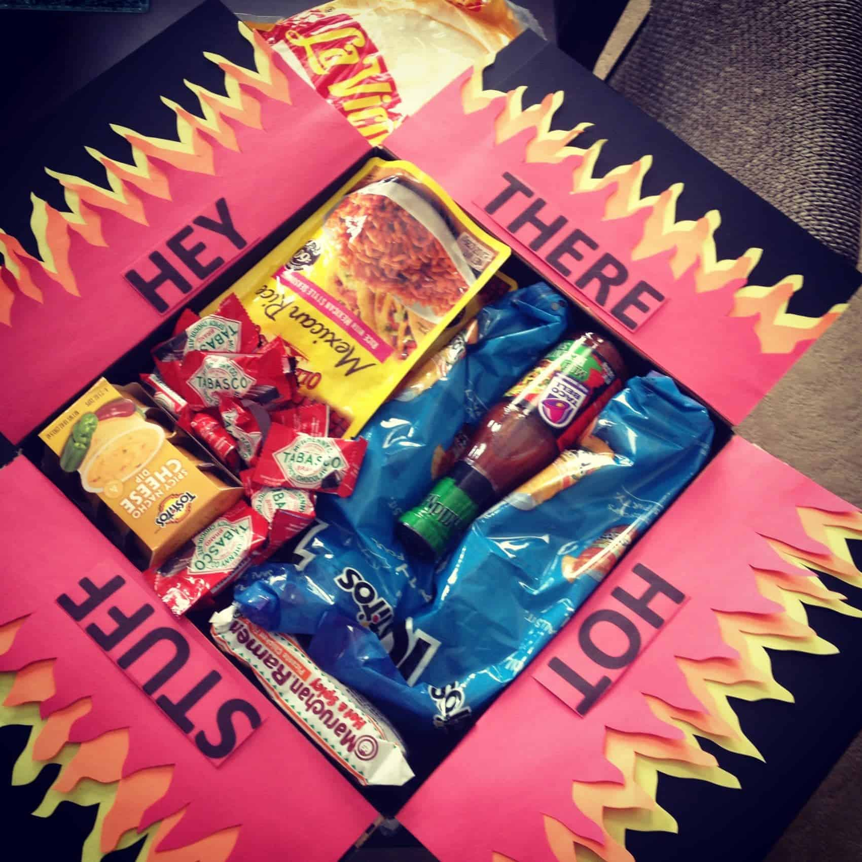 Hey there hot stuff care package with flame paper attached to fold out top filled with spicy foods.