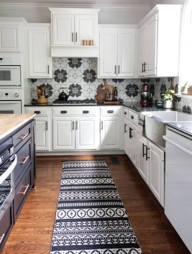 Spacious kitchen with white cabinets, navy blue island,  black and white backsplash tile, and black and white detailed rug.