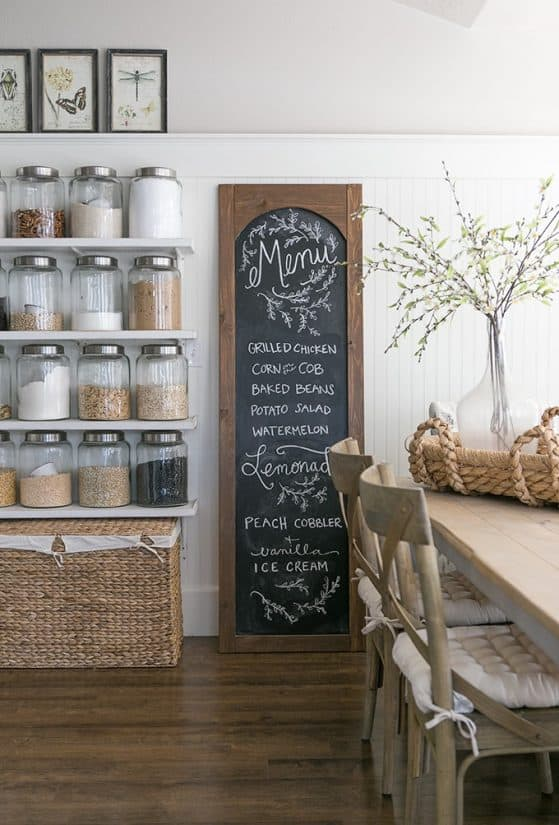 White kitchen with open floating shelf pantry filled with large glass containers of dry good next to tall wood framed chalkboard with menu.