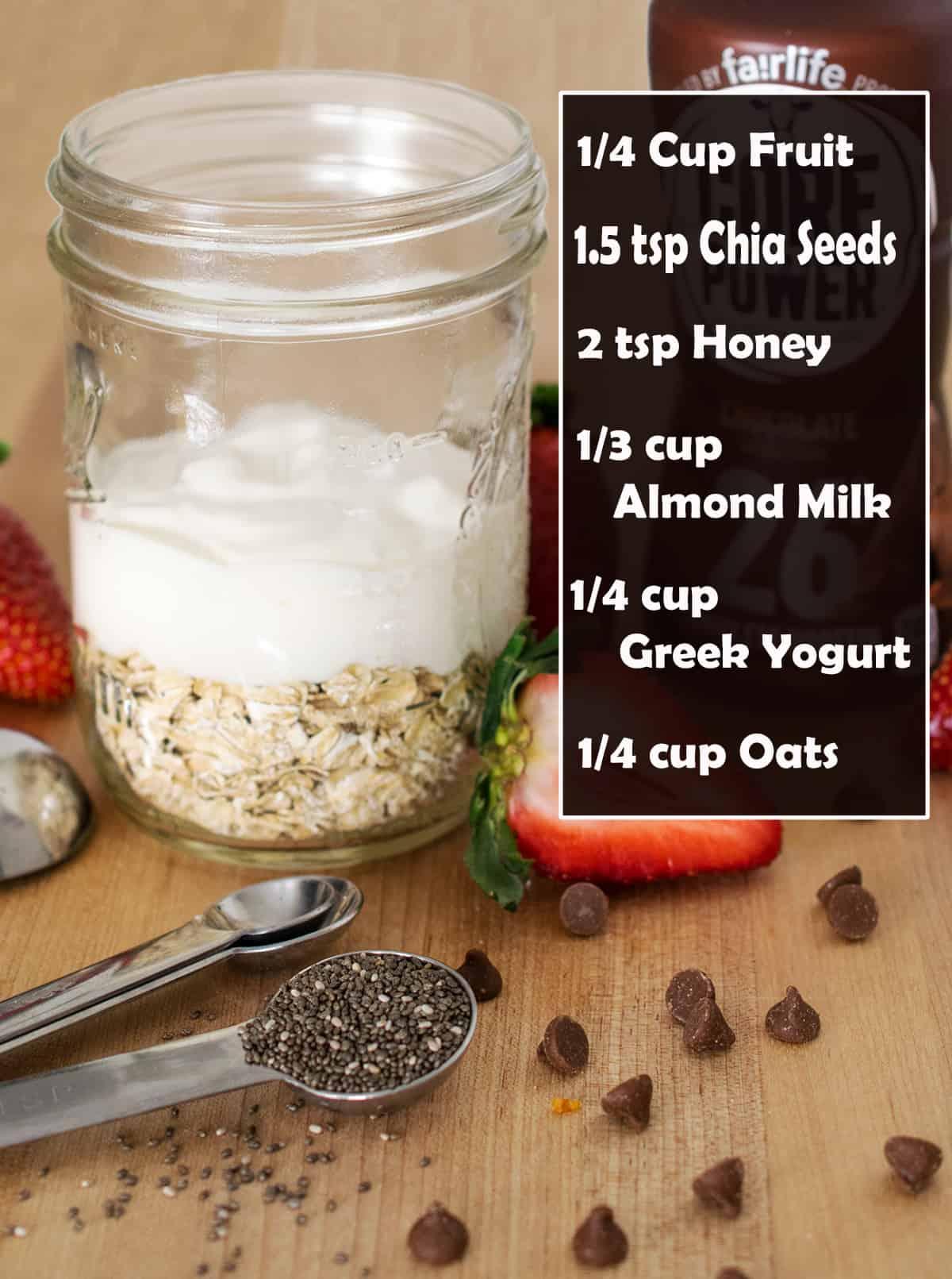 1 mason jars filled with oats, greek yogurt, almond milk, chia seeds, and honey on wooden cutting board.