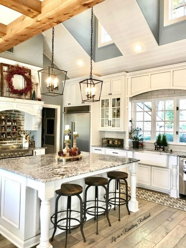 Large modern kitchen with vaulted high vaulted ceilings with windows, white cabinetry, and wide marble top island.