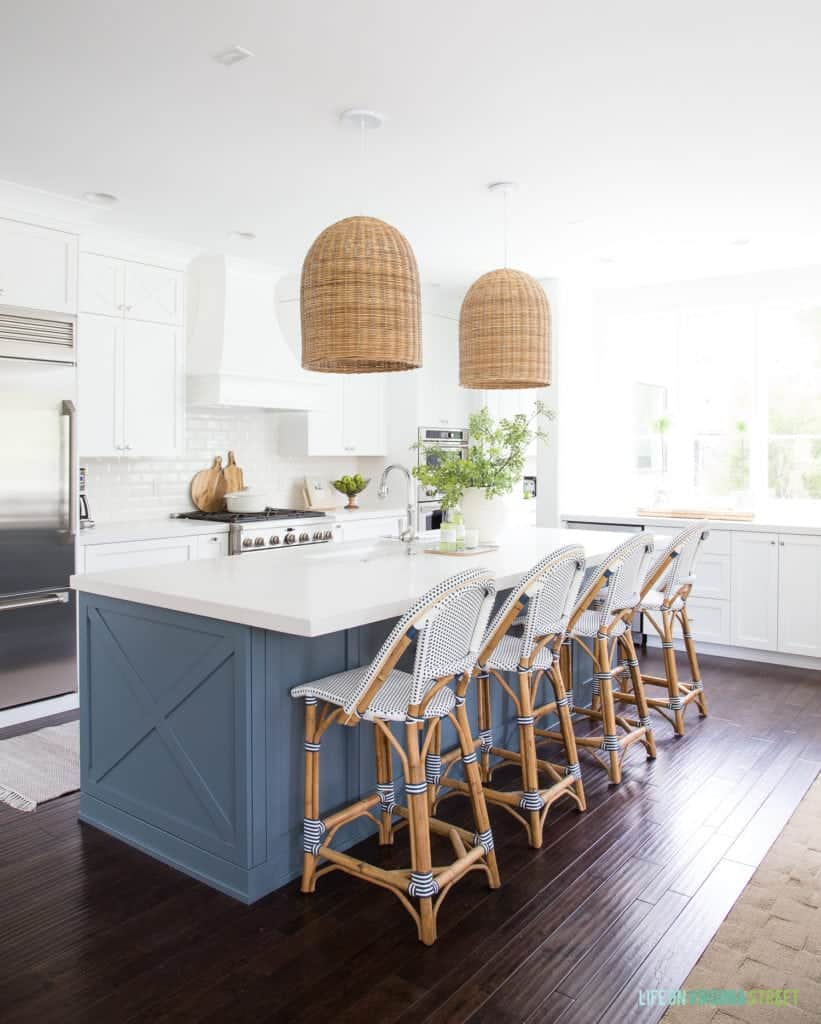 Spacious Open Kitchen with large Blue island, white cabinets, dark wood floors, and wicker pendant lights.