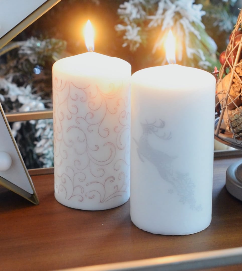 Lit white stamped Christmas themed stamped candles with silver/white accents.
