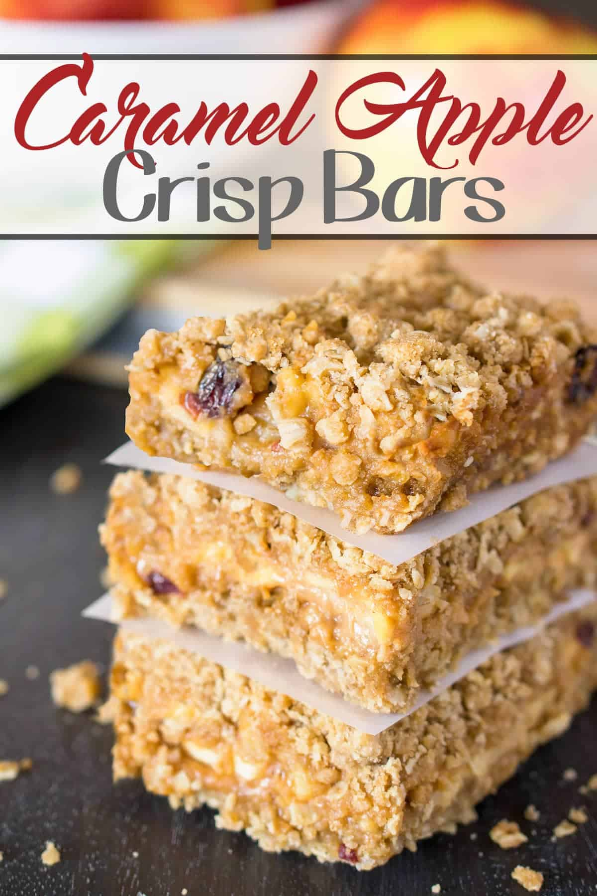 Caramel Apple Bars stacked on parchment paper freshly baked from the oven with post title