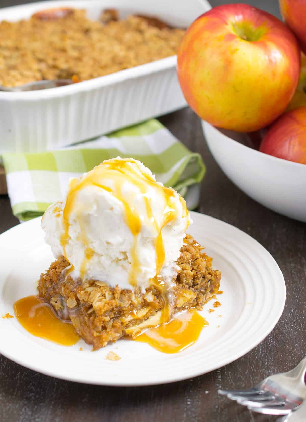 Baked caramel apple crisp bars with vanilla ice cream and caramel sauce on dessert plate beside bowl of apples
