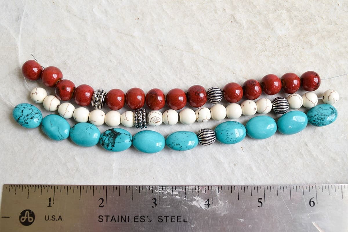 3 strings of white, turquoise, and red beads on white surface next to metal ruler.