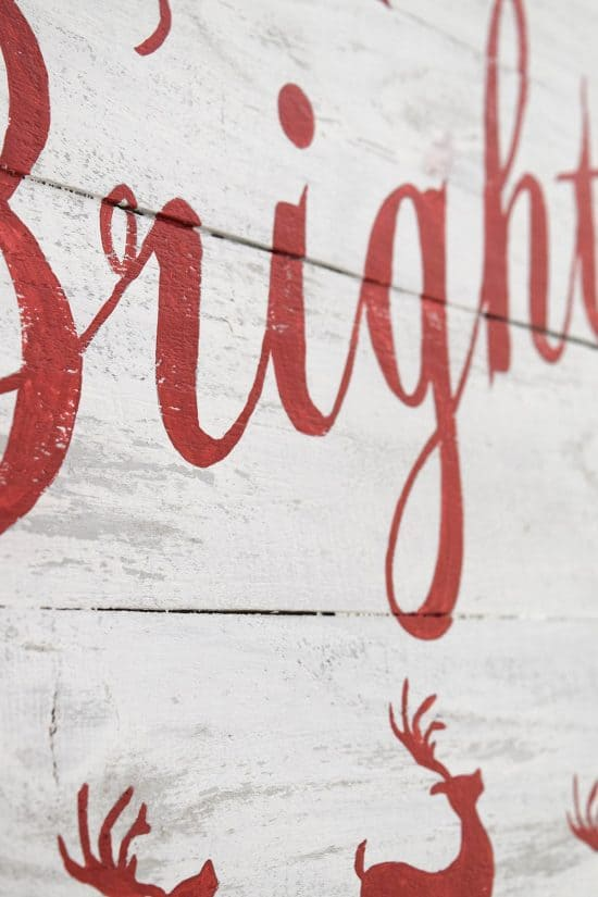 Closeup of Merry and Bright white distressed Christmas sign with red lettering.