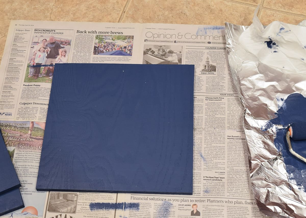 Newspaper with freshly painted navy blue wood square on top next to aluminum foil covered with paint.