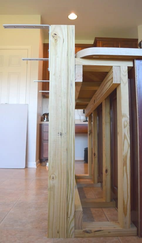 Side view of wood frame for breakfast bar addon on kitchen island with white door in background.