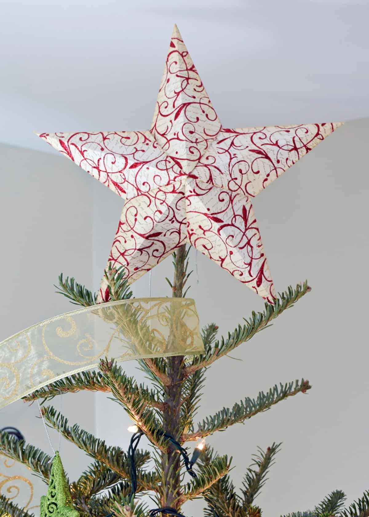 3-D printable white and red star tree topper on top of Christmas tree with gold ribbon garland.