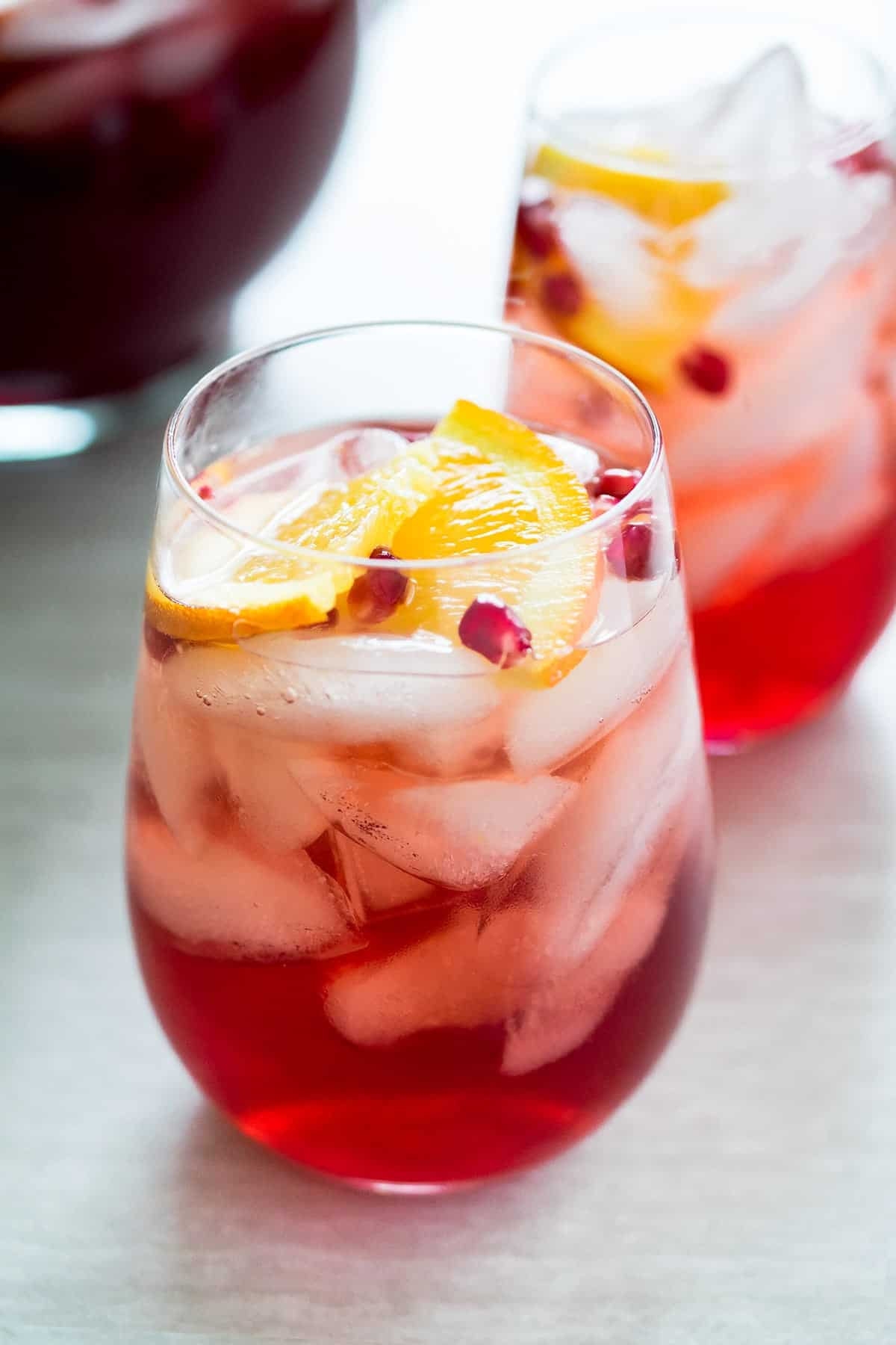 Sparkling holiday punch with vodka, cranberry, pomegranate and triple sec in stemless wine glasses