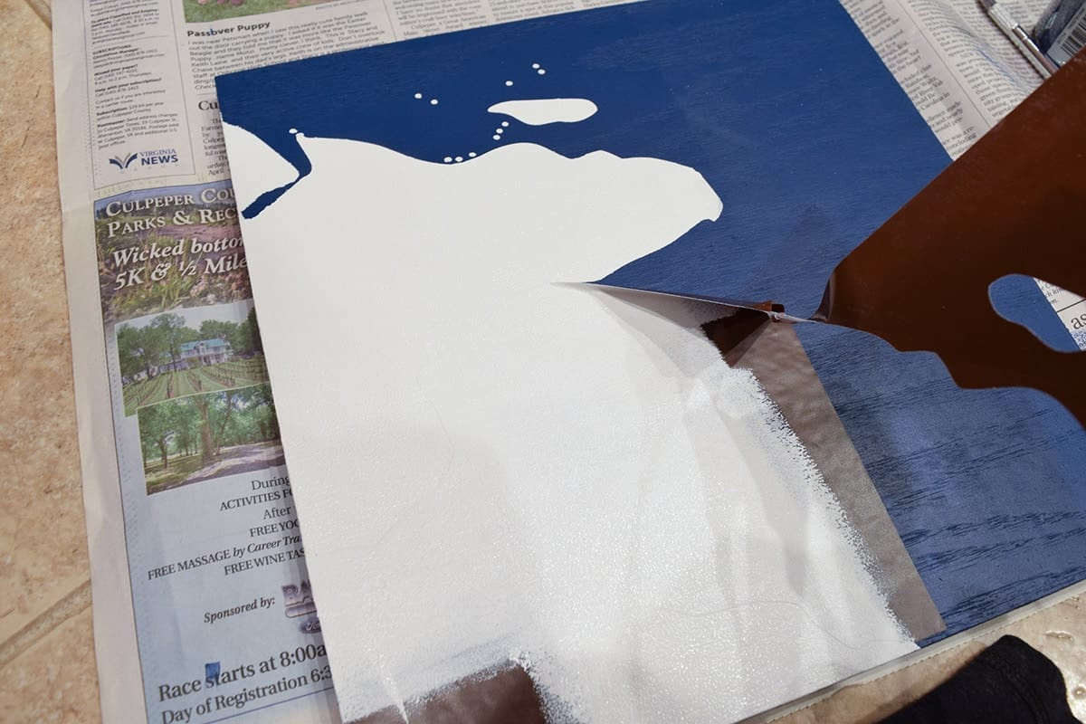 Peeling away vinyl stencil of world map section applied to blue wooden square over newspaper.