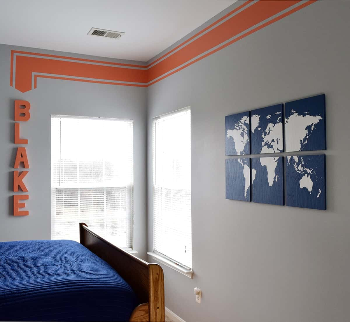 DIY blue and white sectioned world map art on gray wall in boy's room.