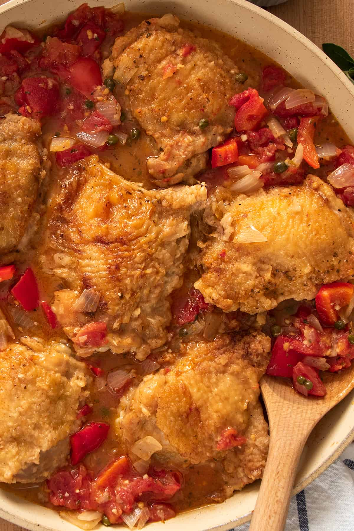 Braised Chicken Cacciatore with peppers and tomatoes stewed in a large skillet.