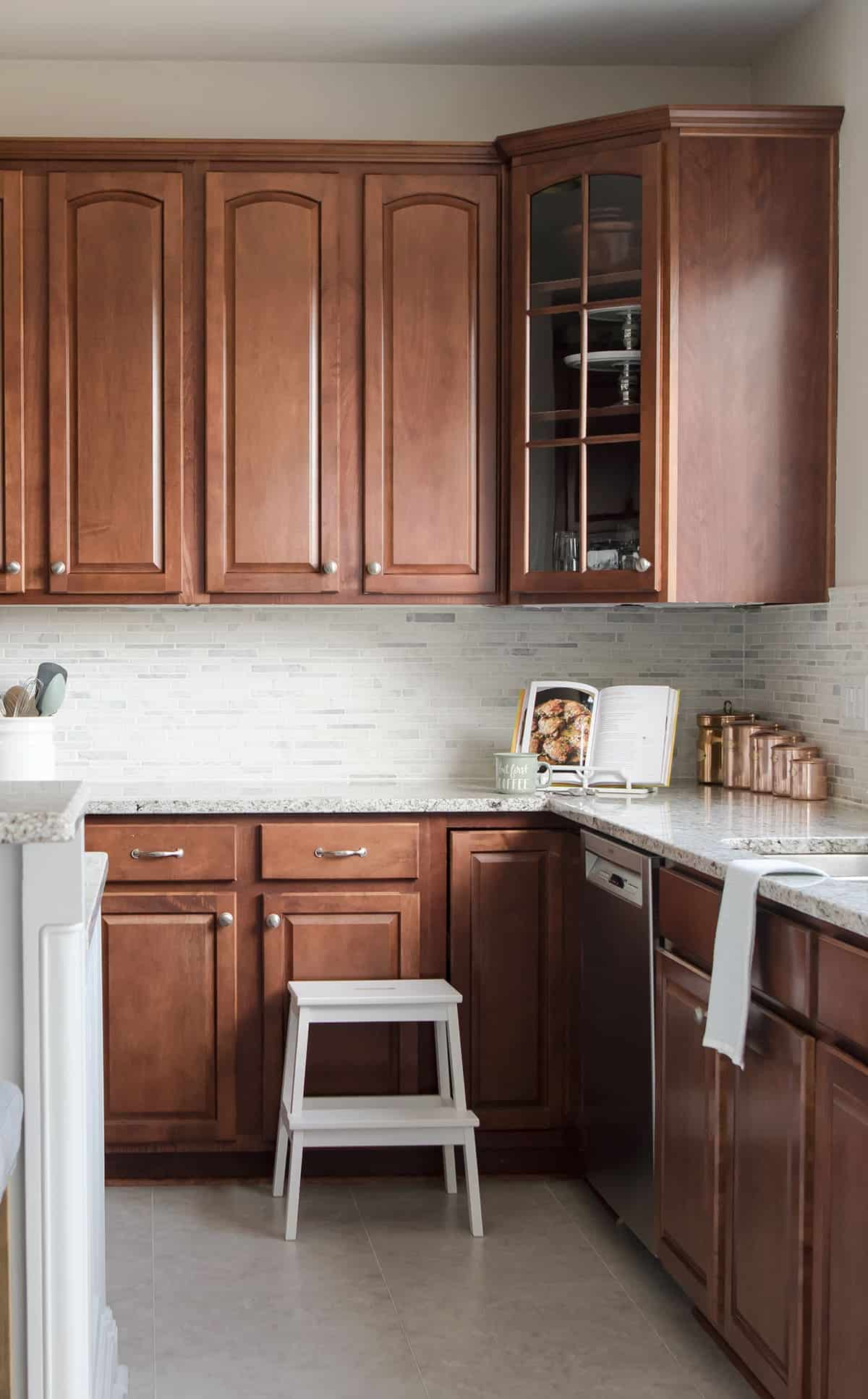 Dark wood cabinets in traditional kitchen with white and gray tile backsplash and light marble countertops.