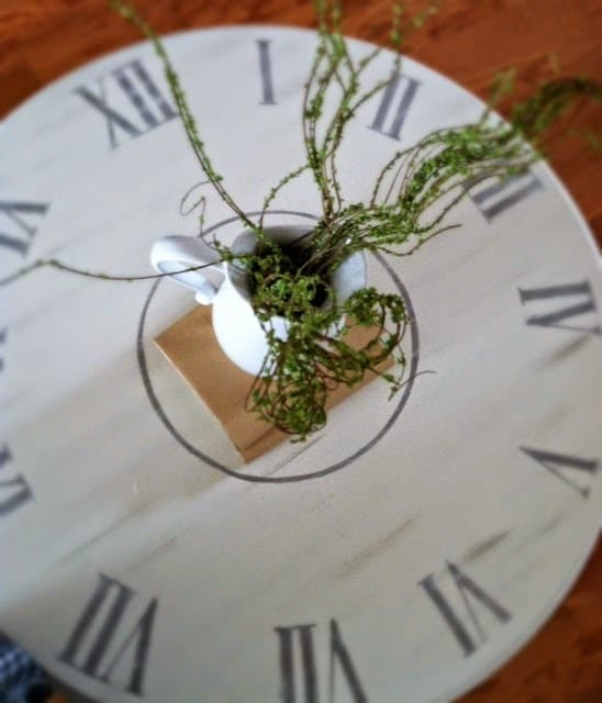 DIY white clock top painted coffee table with plant in white pitcher centerpiece.