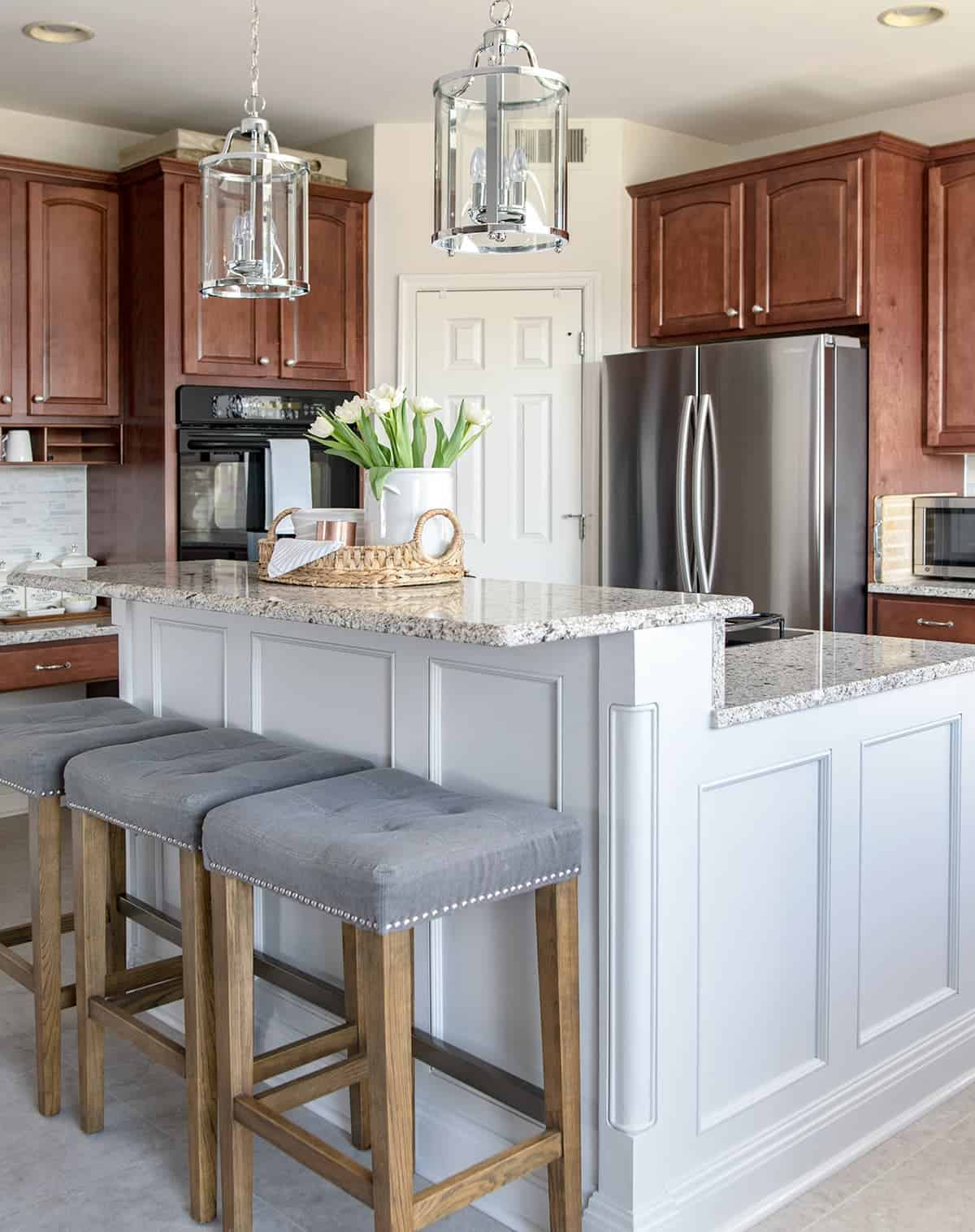 Modern Traditional Kitchen with Wood Cabinets and gray island, light marble countertops, pendant lights, and luxury vinyl floor.