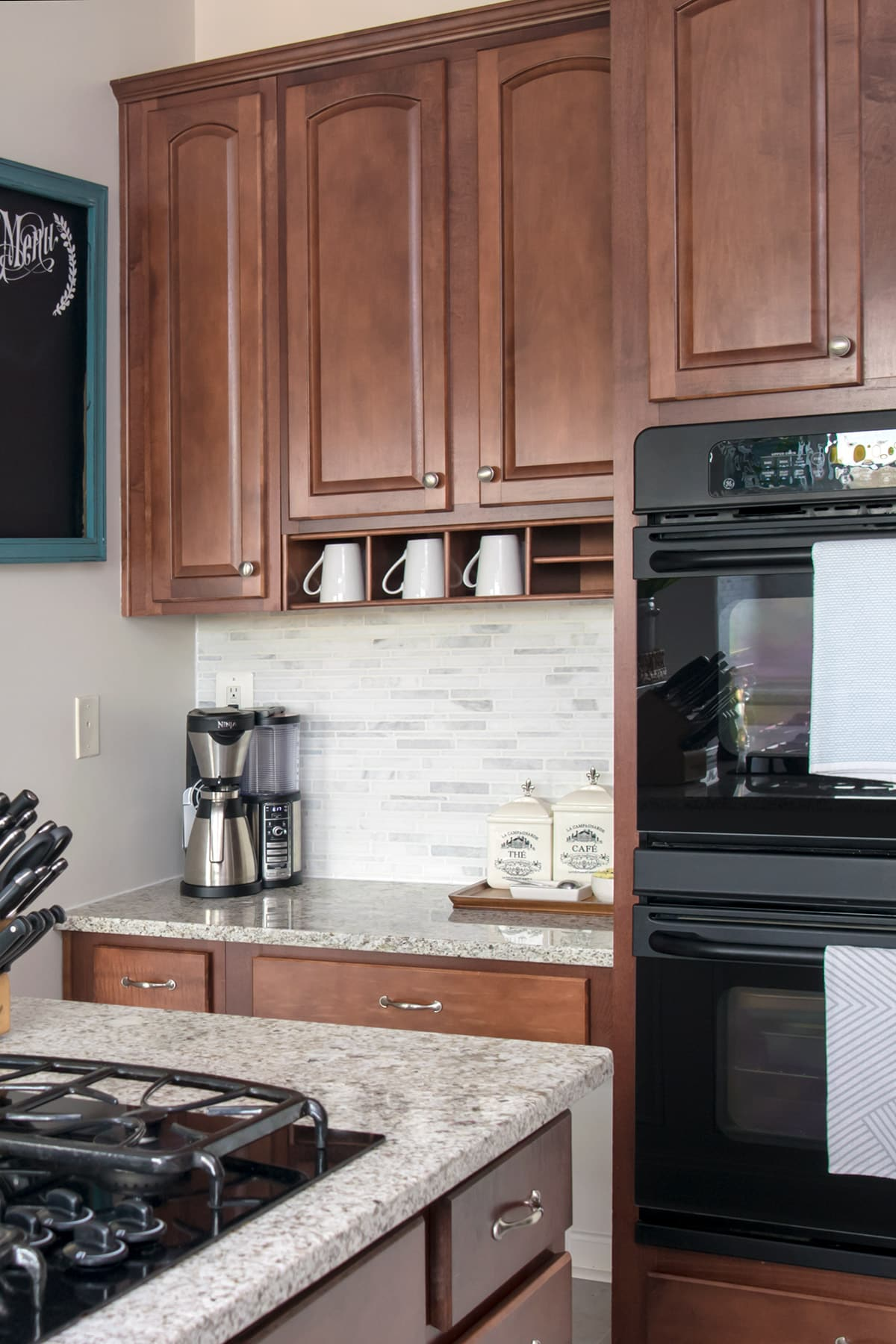 Coffee bar nook by double oven in kitchen. Dark wood cabinets stocked with white coffee mugs above coffee machine, canisters, spoons, and bowl of sweetener.
