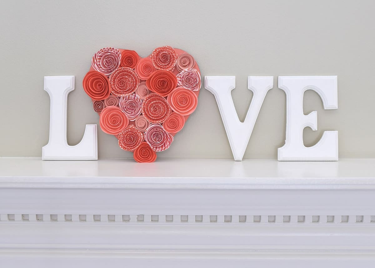 White lettered Valentine's day mantle decor with love message and pink paper flower heart on white mantle.