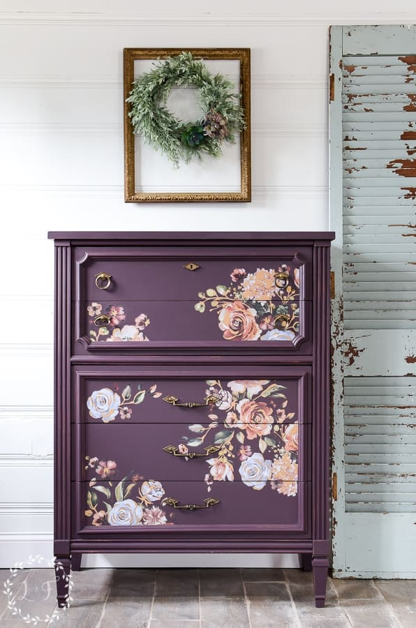 A painted furniture idea of a purple dresser with delicate floral design in front of white plank wall with empty metallic frame with simple wreath.