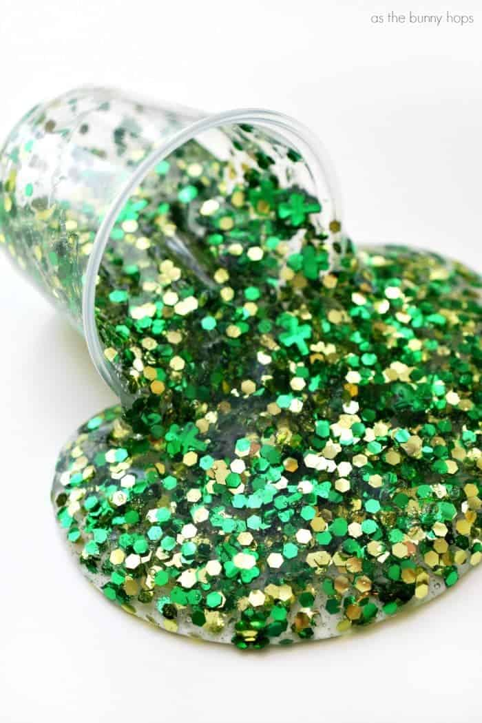 Glitter slime poured onto white surface from clear plastic cup with chunky green and gold glitter.