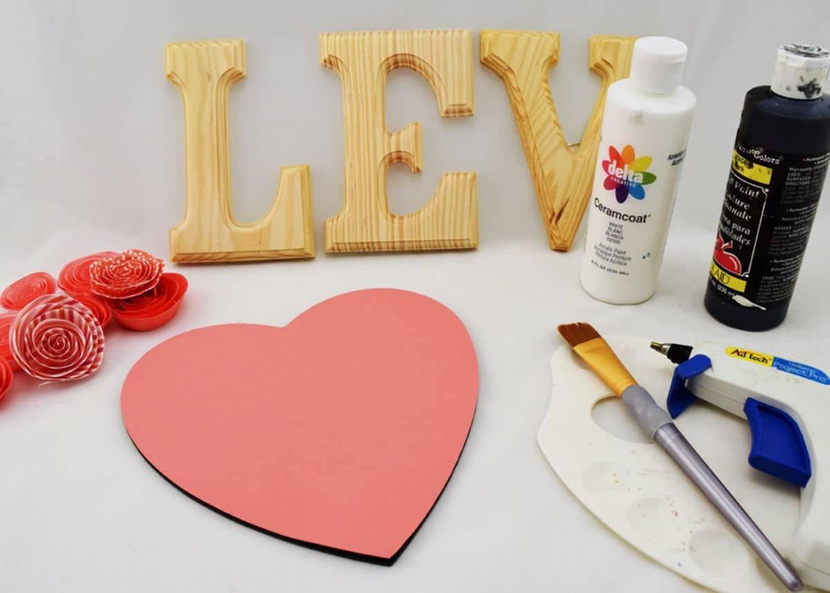 Wood carved letters next to paint bottles, glue gun, paint brush, pink paper flowers, and pink heart cutout.