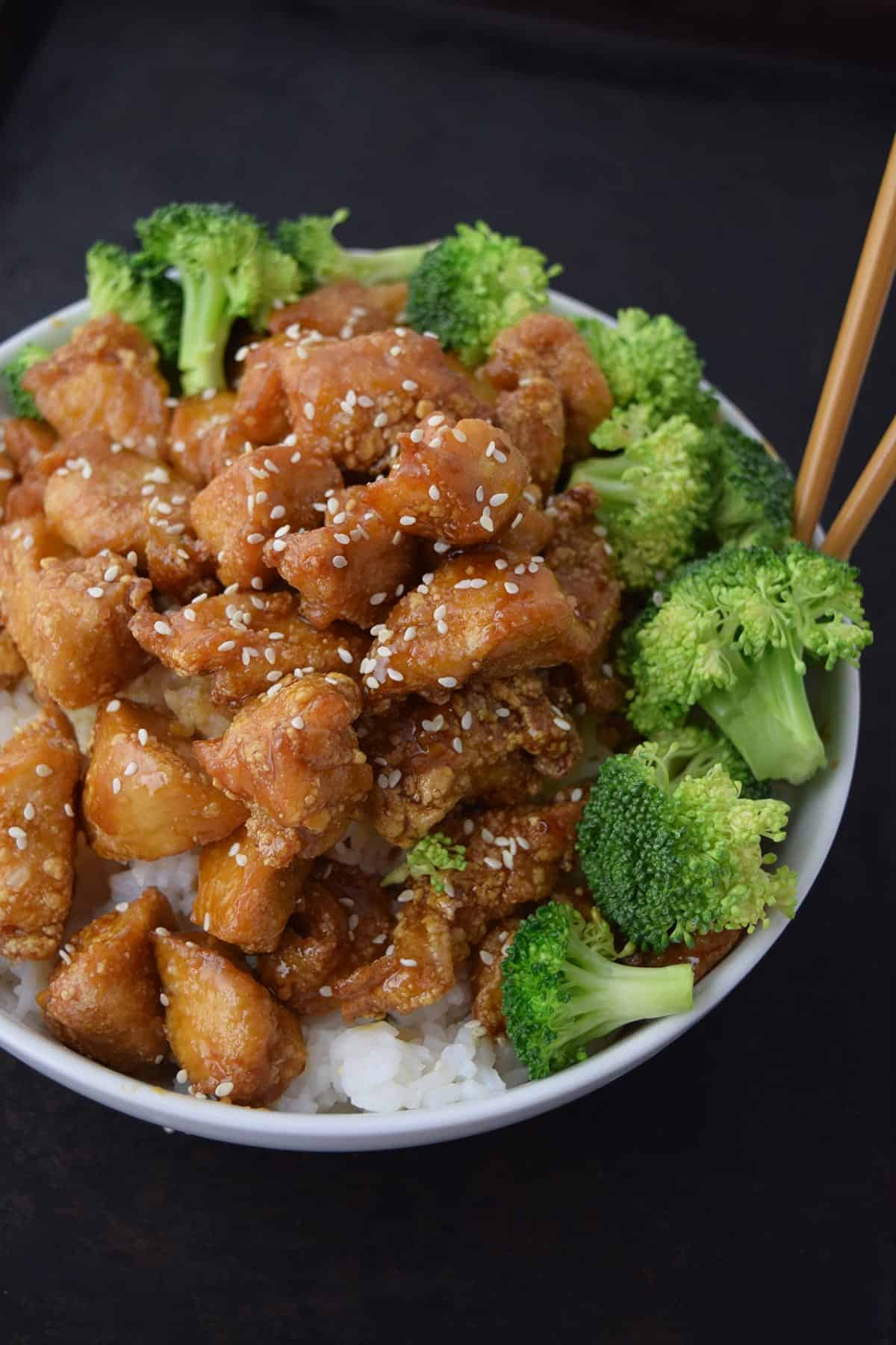 Glazed honey sesame chicken with sesame seeds in white bowl with broccoli with wooden chopsticks on black surface.