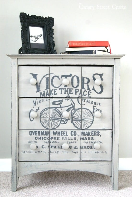 Gray side table with vintage inspired bicycle painting on front drawers in front of gray wall.