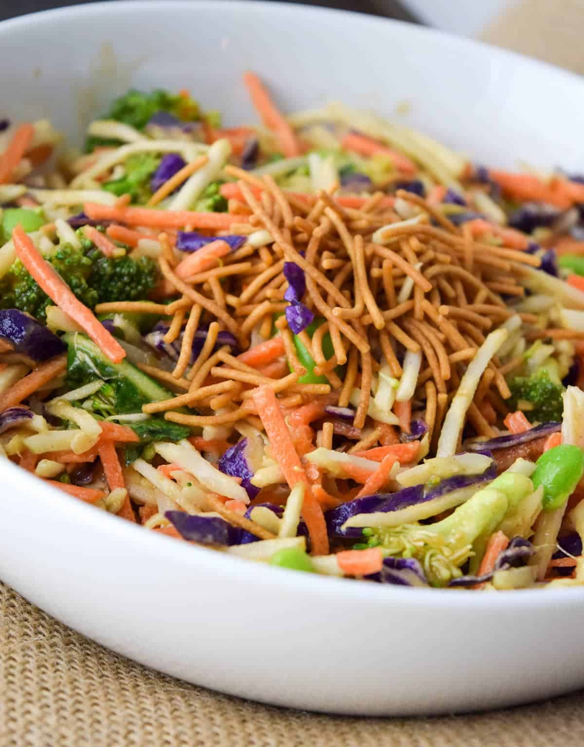 Asian broccoli Slaw with ginger Peanut Dressing topped with crispy asian noodles in white bowl on top of burlap place mat.