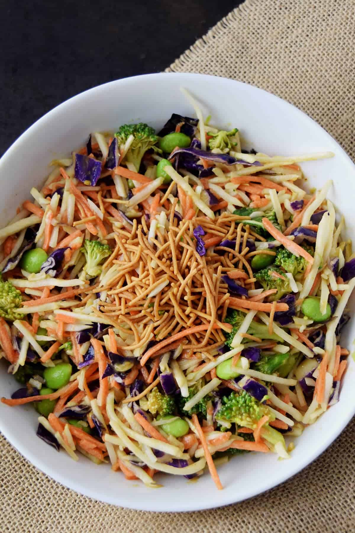 Top down view of Asian Slaw  topped with crispy Rice Noodles in white bowl on top of burlap place mat.