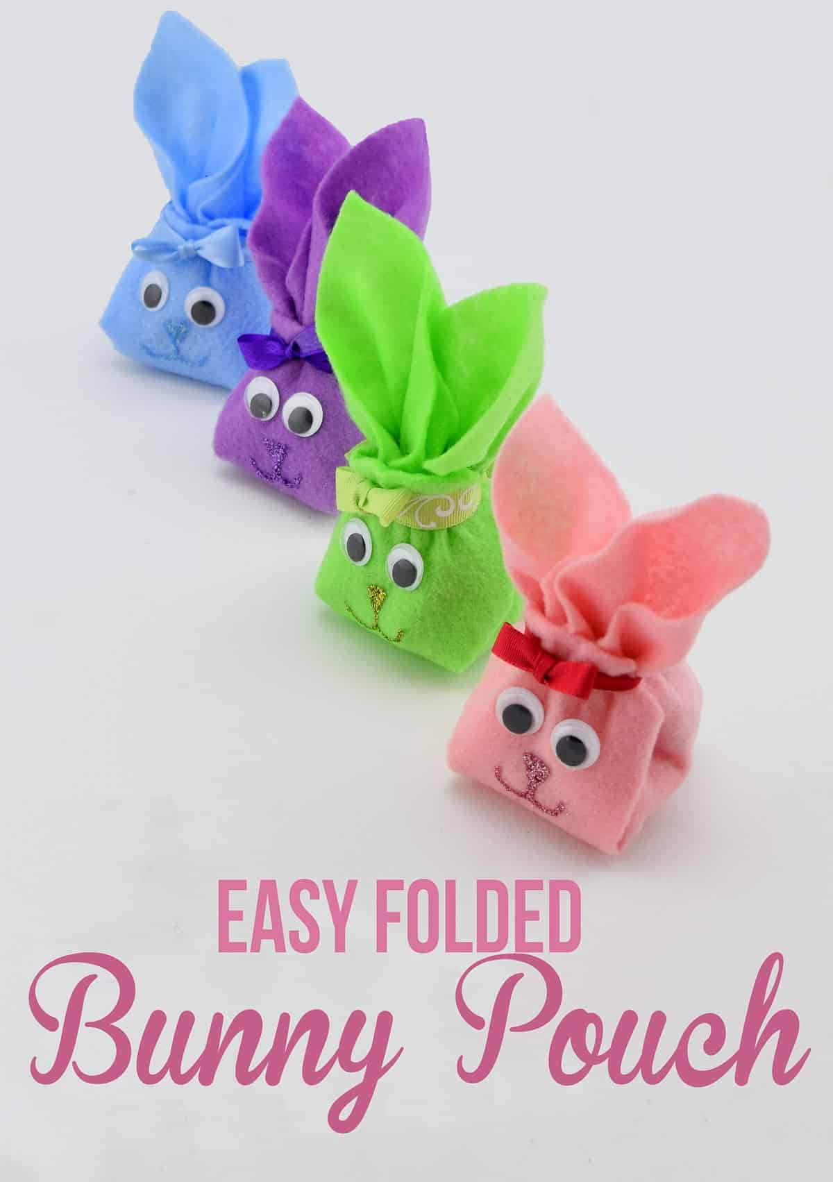 Colorful folded felt bunnies with googly eyes, ribbon, and glitter faces in a row on white surface.