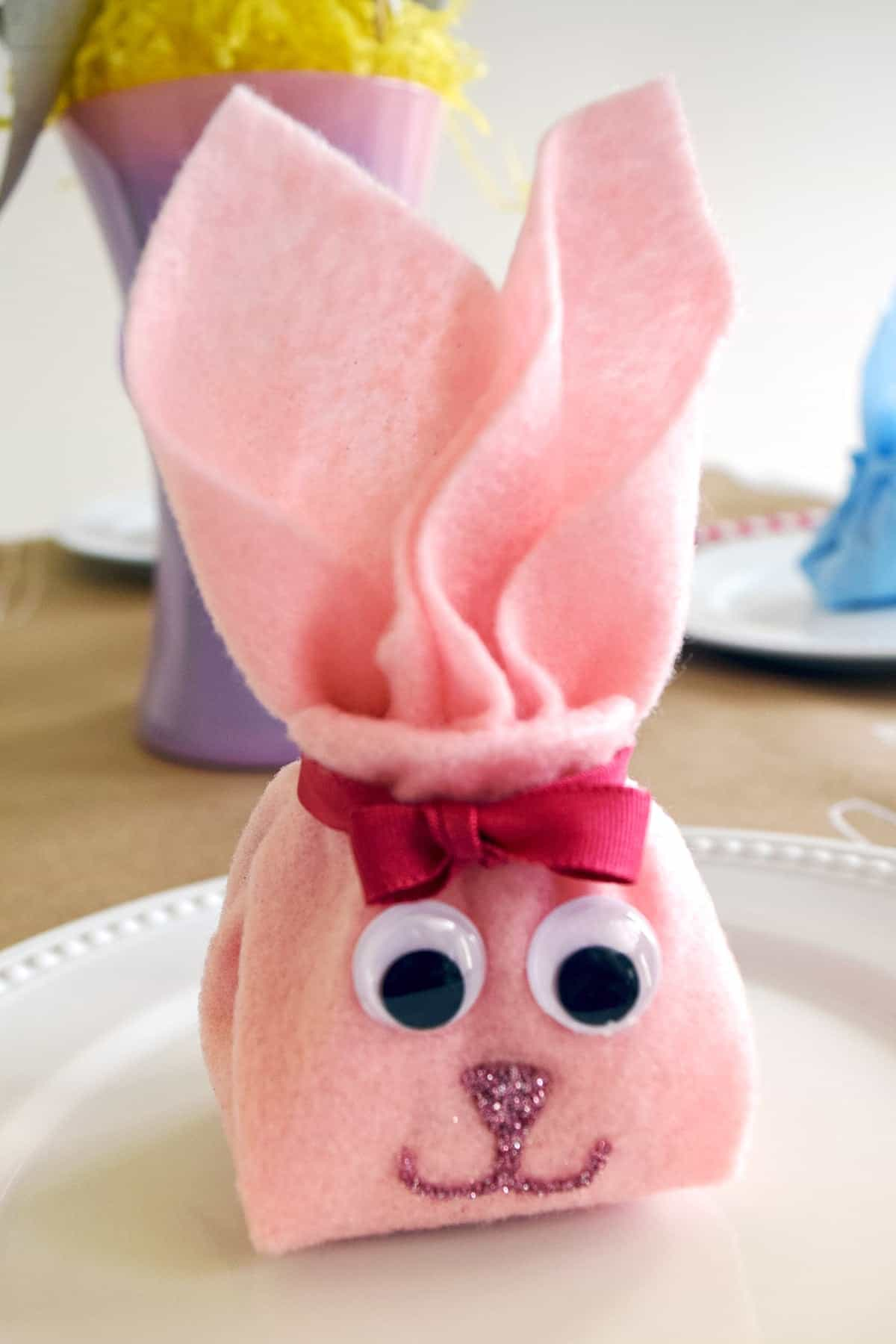 Pink felt napkin folded into bunny shape with ribbon and googly eyes with glitter mouth and nose on white plate.