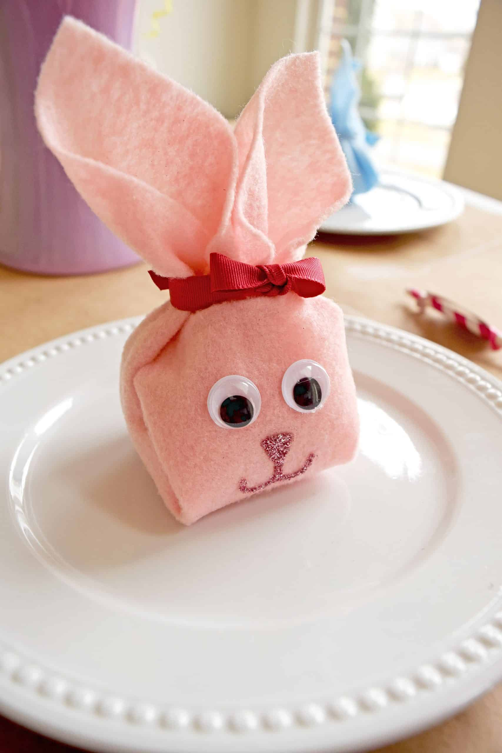 Pink DIY felt bunny pouch with googly eyes on white plate.