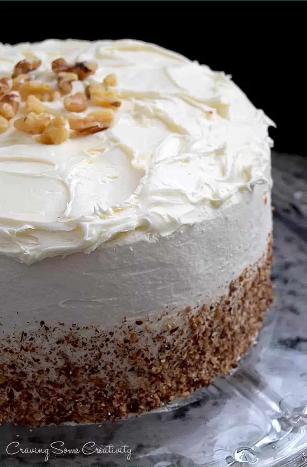 Whole carrot cake with cream cheese frosting, topped with chopped walnuts and crushed walnuts around the side on marble surface.