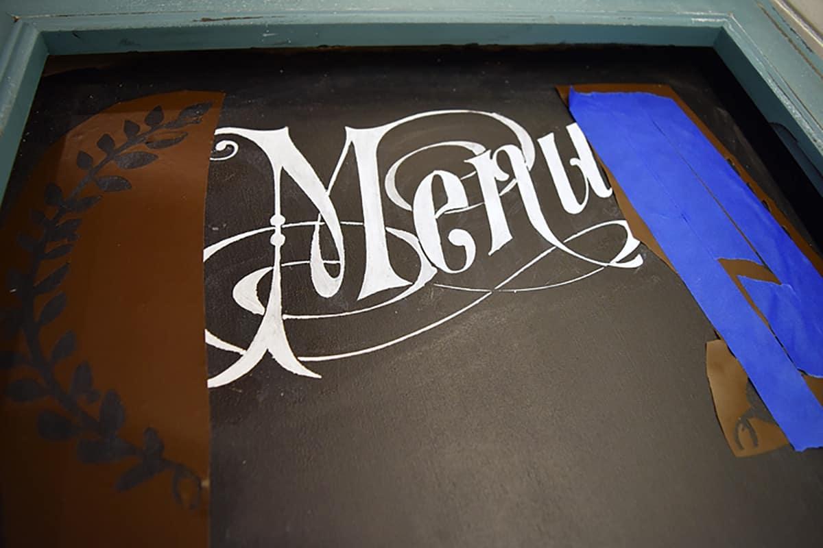 Transferring stencil detail onto framed chalkboard using vinyl and blue frog tape.